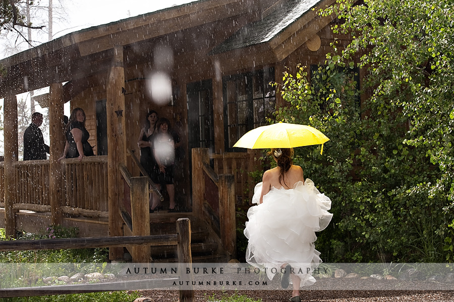 bride with yellow umbrella rain wild horse inn winter park colorado wedding