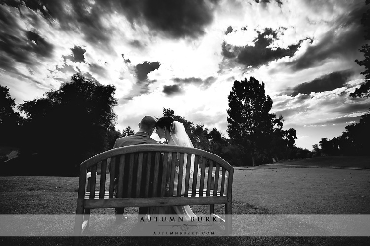 denver country club colorado wedding bride and groom on bench dramatic sky