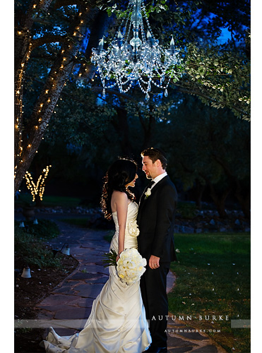 colorado wedding bride and groom under chandelier outdoors at night lionsgate