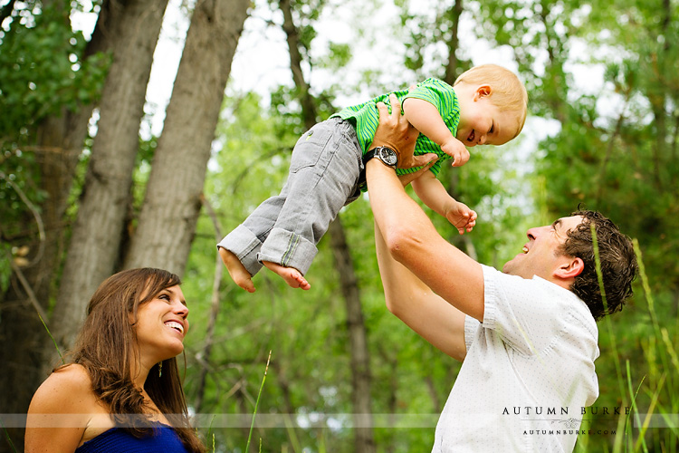 mom and dad and flying baby family portrait outdoors colorado
