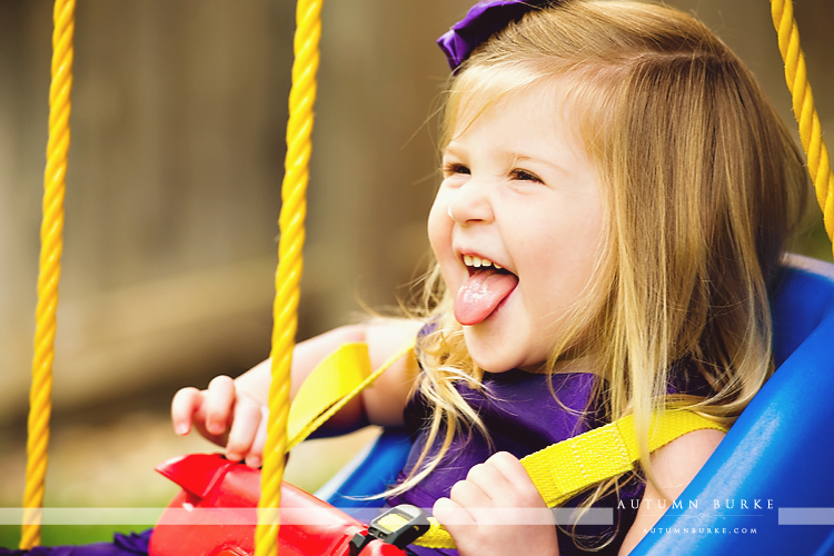 colorado childrens portrait photographer toddler girl in swing laughing lifestyle family portrait