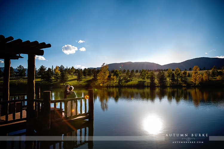 spruce mountain ranch wedding bride and groom by lake with mountains colorado
