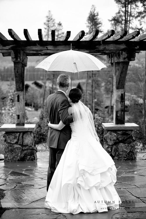 bride and groom with umbrella devils thumb ranch wedding ceremony