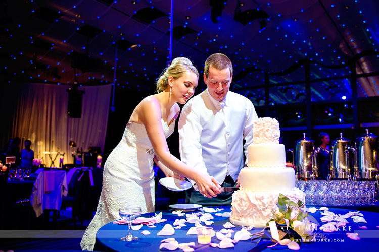 bride and groom cutting cake seawell ballroom wedding dcpa denver colorado